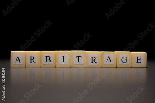 Photo The word ARBITRAGE written on wooden cubes isolated on a black background