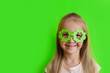 Leinwanddruck Bild - Cute Little blonde caucasian girl in mask of leprechaun shamrock clover glasses for irish St. Patrick's Day on green studio background. Mockup with copy space, template