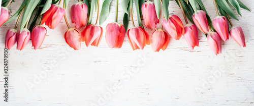Obraz na plátně Pink tulips bouquet border on white wooden background from above