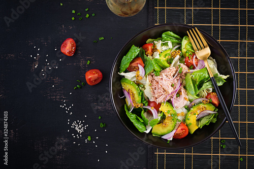 Fototapeta Tuna fish salad with lettuce, cherry tomatoes, avocado and red onions. Healthy food. French cuisine. Top view, copy space, flat lay obraz