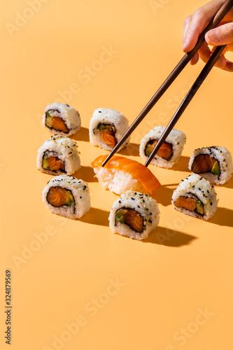 Fototapeta Chopsticks picking nigiri sushi out of maki rolls obraz