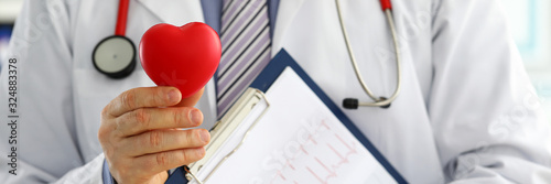 Obraz Male medicine doctor hands holding red toy heart - fototapety do salonu