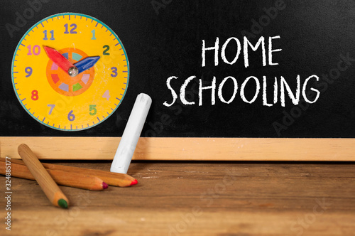 Vászonkép Chalkboard with clock and wooden pencils and word homeschooling