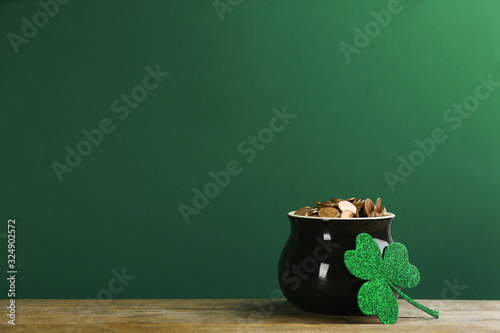 Fotografia Pot of gold coins and clover on wooden table against green background, space for text