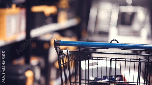 Supermarket aisle with shopping cart in blurred department store background Wallpaper Mural
