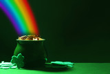 Fototapeta Tęcza - Pot with gold coins and clover leaves on green table, space for text. St. Patrick's Day celebration