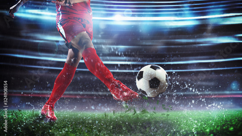 Football scene at night match with player in a red uniform kicking the ball with Poster Mural XXL