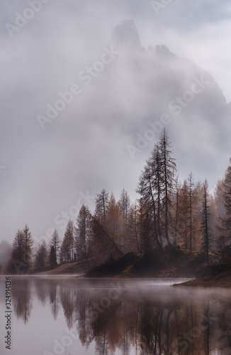 Wall mural - Amazing Federa lake, natural Scenery, during Sunrise. Awesome Landscape. Foggy Dolomites Alps with forest under sunlight. Travel in nature. Beautiful sunrise with Lake and majestic Mountains with fog