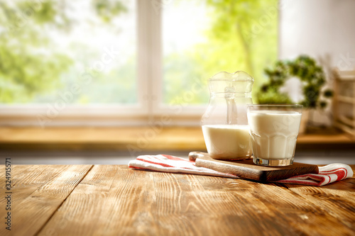 Leinwand Poster Fresh cold milk on wooden table and kitchen interior