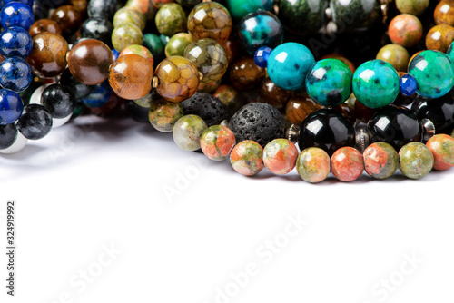 Leinwand Poster Different natural stone beads on a white background, close-up, free space for text