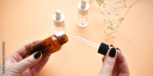 Valokuvatapetti Various bottles of cosmetic oil in the girl's hand pipette, on a pastel pink background