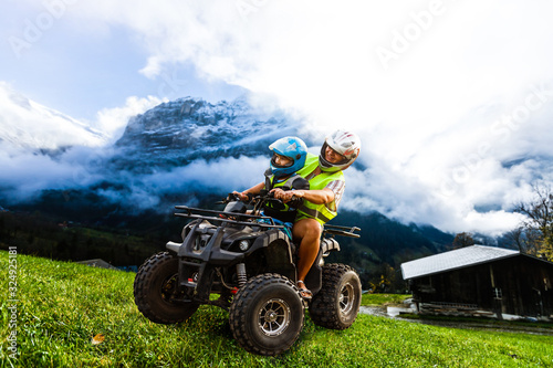Vászonkép Happy family riding and looking quad bike on mountain