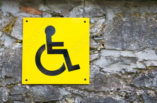 Yellow disabled sign with wheelchair symbol affixed to gray rock background Wallpaper Mural