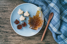 Maple Syrup Top View Of Organic Natural Product From Canada. Maple Leaf Shape Bottle, Soft Candy And Hard Candy Taffy On Rustic Wooden Kitchen Table And Spoon For Cooking