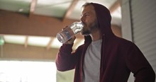 Young Adult Man With Hooded Sweatshirt Drinking Water Resting During Fitness