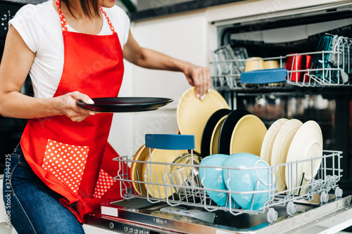 Photo Woman taking out clean dishes from dishwasher machine..