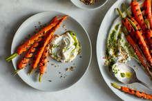 Close Up Of Grilled Carrots Served With Hazelnut Dukkah, Yogurt And Carrot Top Oil On Plates