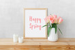 Frame with text HAPPY SPRING, white ceramic vase with bouquet of pink tulips flowers, candles on a wooden table or shelf on a background of light gray wall. Stylish spring home interior decor. Mock up