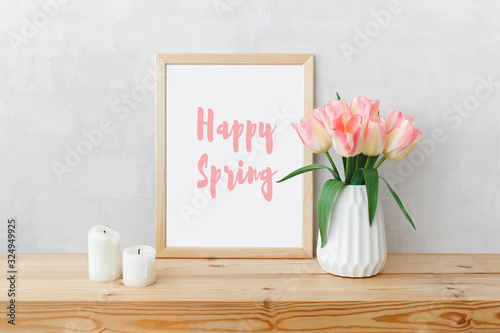 Fototapeta Frame with text HAPPY SPRING, white ceramic vase with bouquet of pink tulips flowers, candles on a wooden table or shelf on a background of light gray wall. Stylish spring home interior decor. Mock up obraz
