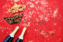 Two Champagne Bottles, Carnival Mask And Confetti On Red Background. Flat Lay Of Purim Carnival Celebration Concept.