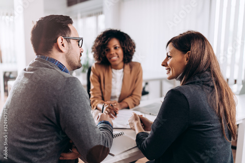 Fototapeta Couple consulting with a female financial manager at the bank obraz