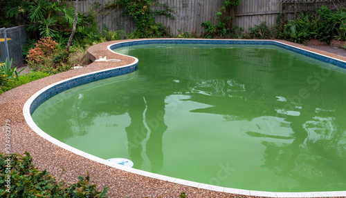 Valokuva green dirty pool algae water in a suburban backyard
