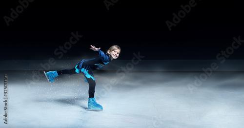 obraz PCV view of child figure skater on dark ice arena background