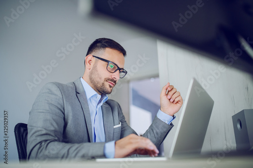Obraz Hardworking classy handsome businessman in suit and with eyeglasses sitting in his office and using laptop. - fototapety do salonu
