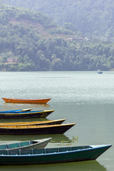 Fototapeta Rzeki i Jeziora small boats of various colors, on the blue surface of the lake. Green hills and clouds on the background. Vacation in Nepal.