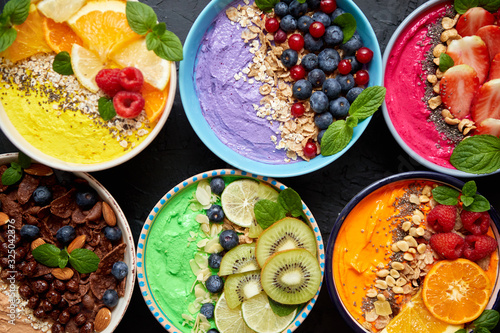 Fototapeta Various healthy fresh smoothies or yogurts in bowls. With strawberries, kiwi, chia, blackberries obraz