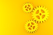 Leinwanddruck Bild - Three yellow mechanical gear cogwheels over yellow background - industry, teamwork, solution or cooperation minimal modern concept