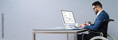Obraz Businessman Working In Office Sitting On Wheelchair - fototapety do salonu