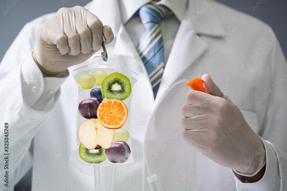 Fototapeta Doctor Holding Saline Bag With Fruit Slices Inside In Hospital