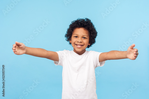 Photographie Come here, free hugs! Portrait of lovely good-natured little boy with curly hair in white T-shirt smiling excitedly and holding hands wide open to embrace, greeting