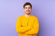 Caucasian Man Isolated On Purple Background Keeping The Arms Crossed In Frontal Position