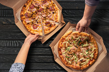 Overhead View Of Hands Taking Pizza From Cardboard Box