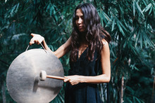 Young Beautiful Woman Holding And Playing Gong Outdoor