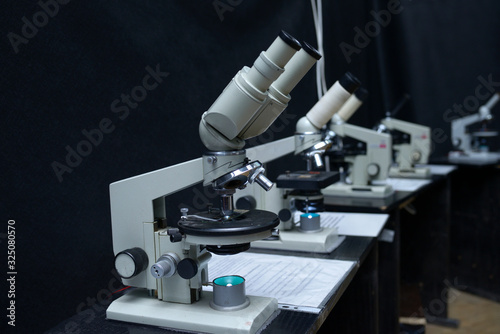 Valokuva Microscopes set on the worktable of the school lab, black background