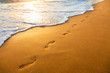 canvas print picture - beach, wave and footprints at sunset time