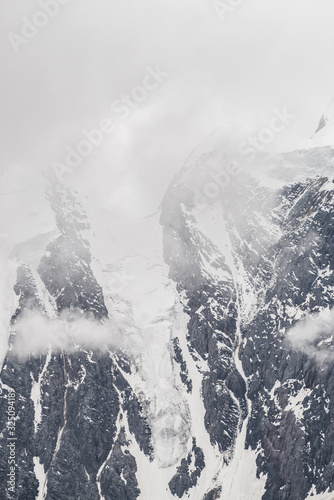 Fototapety, obrazy: Atmospheric minimalist textured alpine landscape with massive glacier on big mountain in low clouds. Background of snowbound mountainside. Cracks on ice. Majestic foggy misty scenery on high altitude.