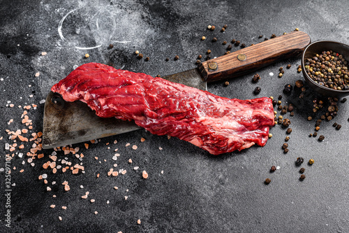 Fototapeta Raw skirt, machete steak on a meat cleaver. Black background. Top view obraz