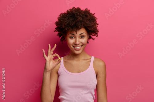 Fotografía Pretty dark skinned female model shows okay gesture, reassures everything goes e