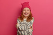 canvas print picture - Waist up shot of overjoyed little girl hugs herself, crosses arms over body, laughs out, wears pink hat and striped jumper, expresses self love, has foxy hair, closes eyes with great pleasure
