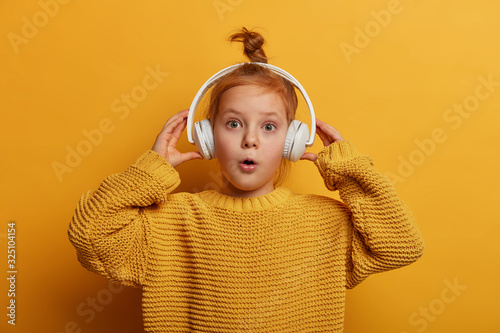 Fototapeta Surprised ginger kid listens audio track in headphones, impressed by loud sound, opens mouth with wonder, wears oversized knitted sweater, isolated on yellow wall. Children and hobby concept obraz