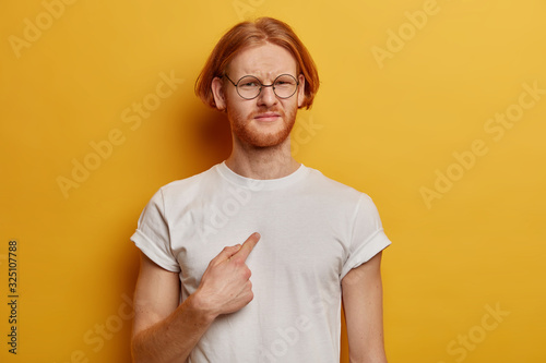 Canvas Waist up shot of dissatisfied bearded man with ginger bob hairstyle points at hi
