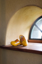 Two Yellow Wooden Shoes In Beautiful Soft Light From A Old Fashioned Farm Window Against A Yellow Wall