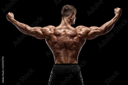 Tablou Canvas Muscular man showing back muscles, isolated on black background