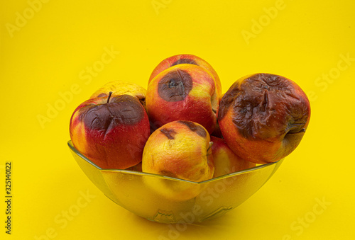 Fotografie, Tablou rotten apples in a vase on the yellow background isolate
