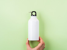 Zero Waste Concept - White Metal Reusable Water Bottle Held By Female Hand. Flat Lay On Green Pastel Background