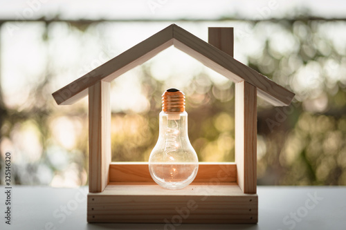 Photo Light bulb with wood house on the table, a symbol for construction, Creative light bulb idea, power energy or business idea concept ecology, loan, mortgage, property or home